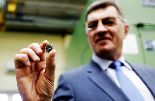 Lietuvs premjers Aļģirds Butkevičs ar jauno Lietuvas eiro monētu