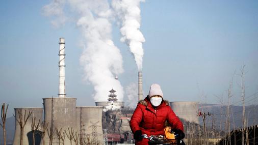 Cilvēki cenšas sevi pasargāt, kā var - sieviete brauc ar riteni tērauda rūpnīcas tuvumā Pekinā