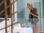 Полуобнаженная модель наслаждается утренним кофе на балконе в Каннах