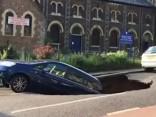 Milzu caurums Londonas ielā aprij automašīnu