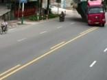 Motobraucējam gandrīz uzgāžas kravas auto piekabe