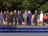 Kanādas latvieši pie Brīvības pieminekļa vēro ziedu nolikšanas ceremoniju